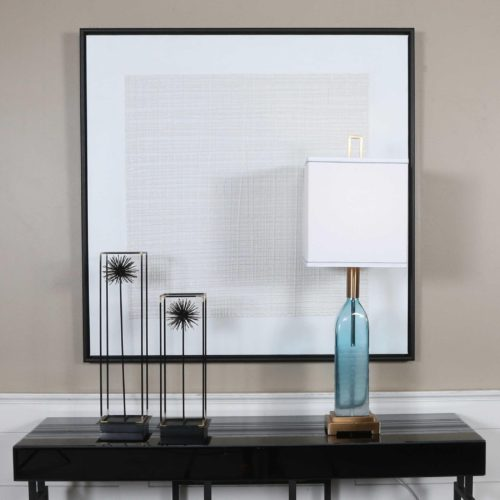 calming artwork pieces above a black console table with a blue lamp.