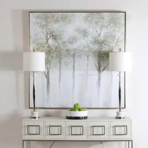 serene artwork pieces above a console table with lamps.