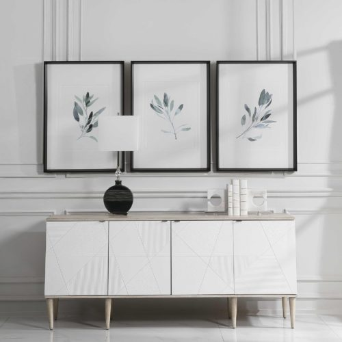 artwork pieces hanging above a mid century console table with a lamp.