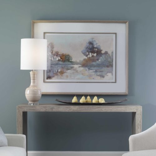 artwork pieces above the living room console table with a lamp.