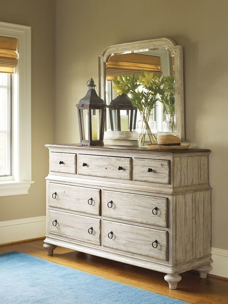 Distressed wood small dresser by Kincaid with a mirror, lamp, and plant for decoration.