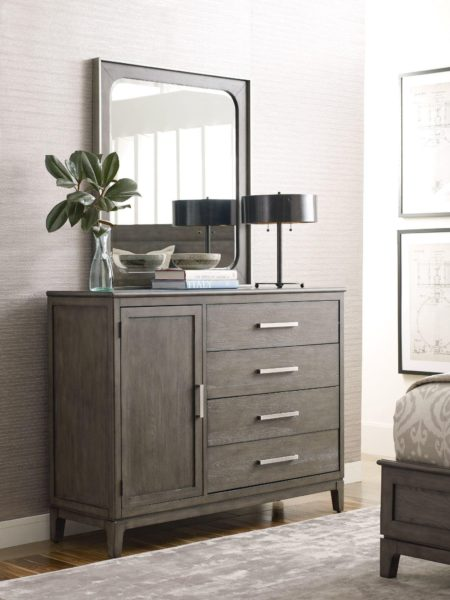 A dark wood small dresser by Kincaid with a mirror, plant, lamp and books on top.