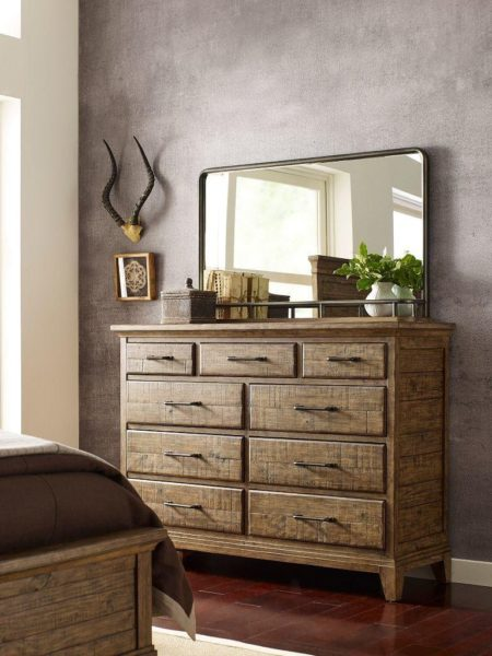 Nine drawer small dresser with a light wood color by Kincaid with a mirror and other decorative pieces.