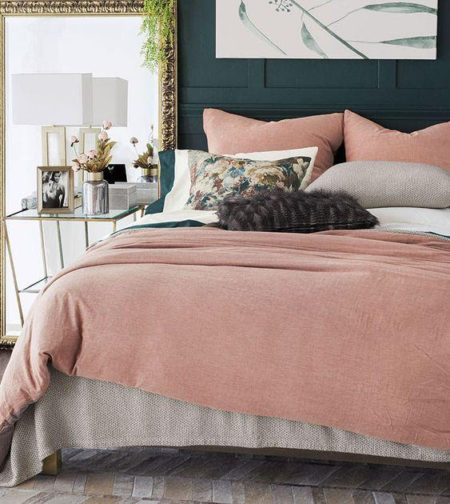 pink bedding with bedroom accessories on a nightstand including a lamp and picture frame.