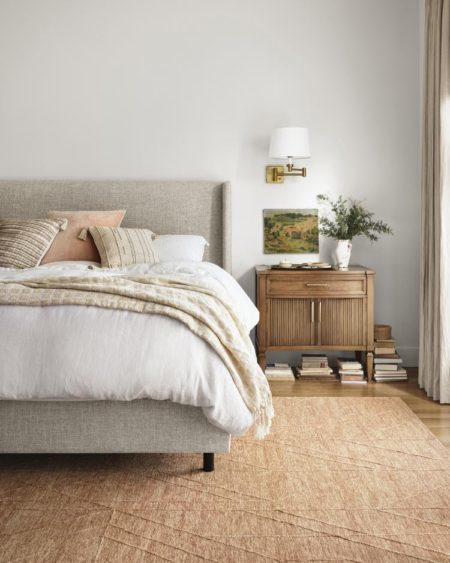 bedroom set up with bedroom accessories like a plant and hanging photo over the nightstand.